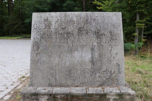 """Tablica upamiętniajaca ofiary z lat 1942-44. Na tablicy napis: """"Lisie Jamy miejsce w głębi lasu, gdzie w latach 1942-1944 żołnierze niemieccy zamordowali ok. 2500 ludzi - Żydów, Cyganów i Polaków. To miejsce największej zbrodni hitlerowskiej na ziemi garwolińskiej."""""""