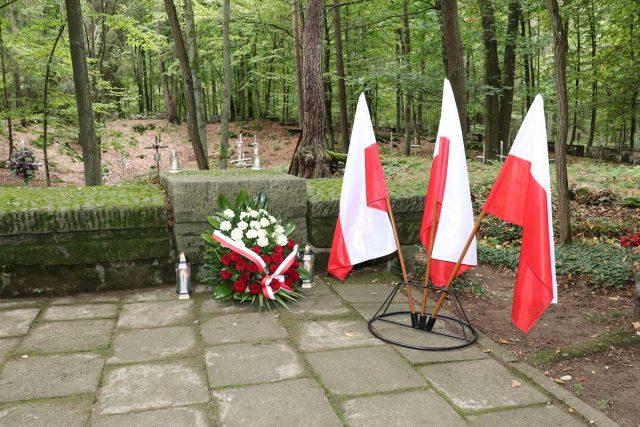 Miejsce pamięci ofiar reżimów totalitarnych - tzw. Lisie Jamy. Zapalone znicze, wieniec i flagi państwowe.